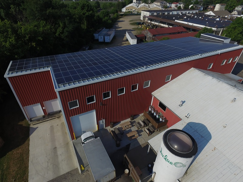 "alt=""aerial photo of Jackie O's with solar panels on the new building"""