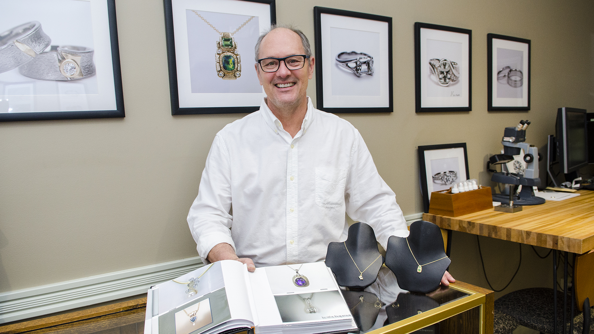 The owner of Keith Chapman Jewelers standing by two necklaces he designed.