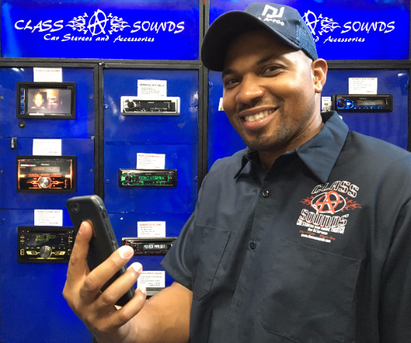 owner of Class A Sounds standing in front of car stereo systems holding a smart phone