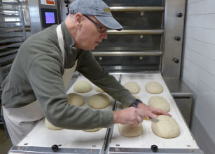 owner of Athens Bread Company scoring loaves of bread before they go into the oven