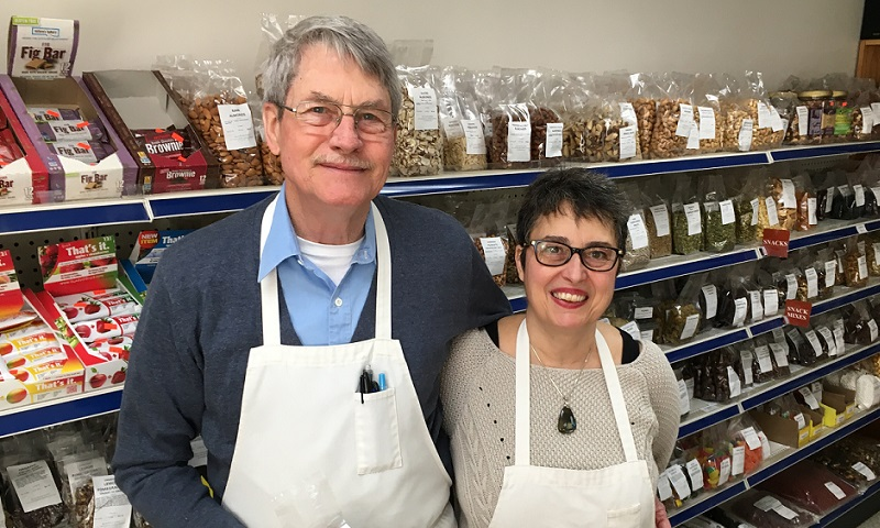 owners standing in front of an isle of bulk food items