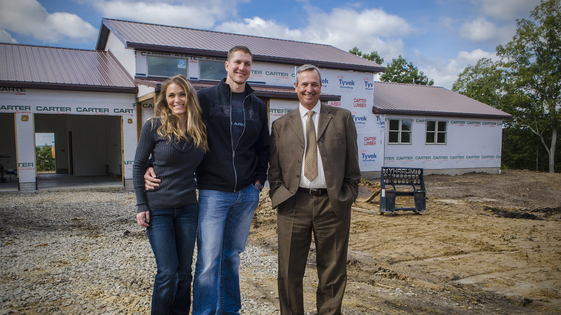 A couple standing in front of their new home, which is under construction, with their lender.