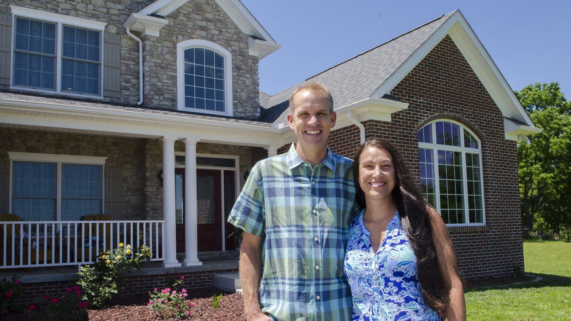 A man and woman standing in front of their newly constructed home.